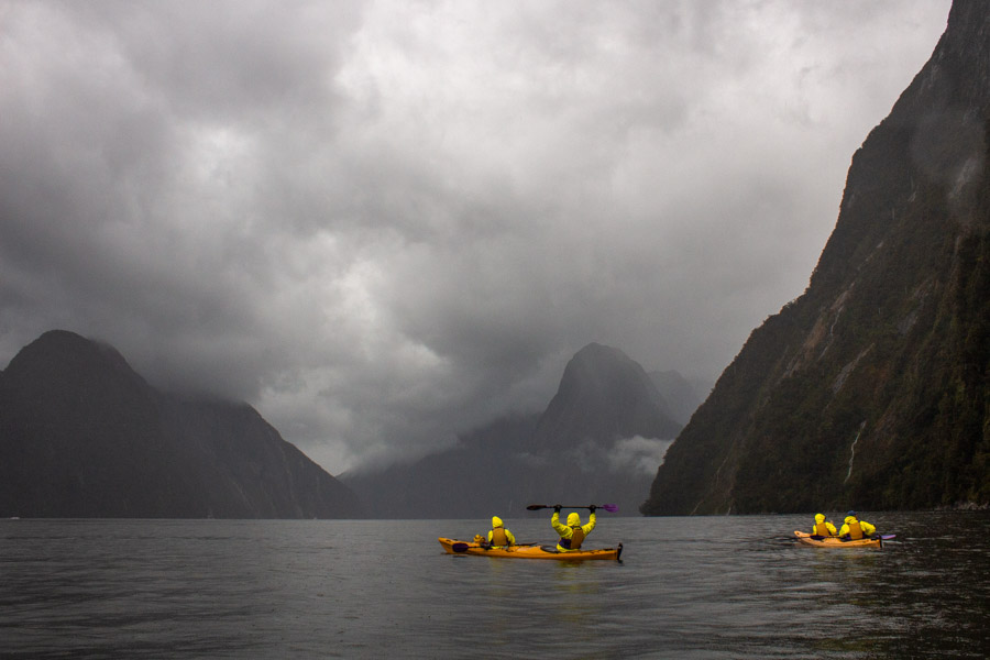 Kayaking boats on Milford Sound on a cloudy and stormy day