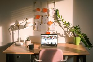 Desk with The Wandering Suitcase Pinterest Displayed on Laptop screen